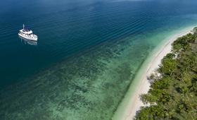 phuket plage sable blanc foret bateau eau turquoise